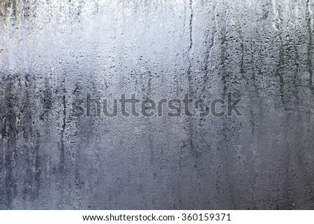 Closeup shot of a steamy window with water drops made in dull day. - stock photo