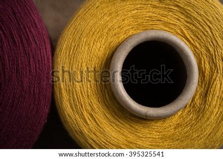 Closeup shot of a yellow thread and spool hole alongside spool of maroon thread - stock photo