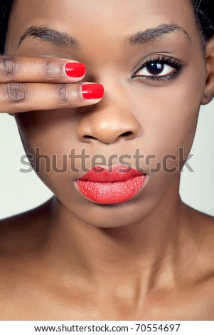Closeup shot of a young woman with natural makeup, red lips and matching manicure - stock photo