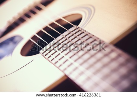 Closeup shot of acoustic guitar with shallow depth of field.