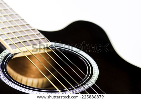 Closeup shot of an acoustic guitar over white background.