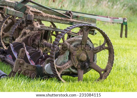 Closeup shot of an old rusty golf course mower on a green meadow