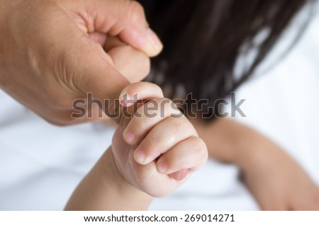 closeup shot of baby's hand holding her mother's finger tight - stock photo