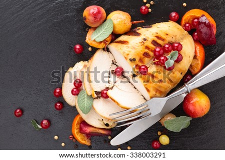 Closeup shot of baked chicken breast with sage and baked fruits on slate. - stock photo