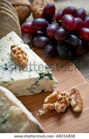 Closeup shot of blue cheese with walnuts and grapes - stock photo