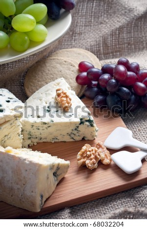 Closeup shot of blue cheese with walnuts and grapes, closeup shot - stock photo