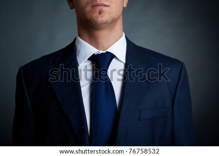 Closeup shot of business suit on a man, over dark background - stock photo