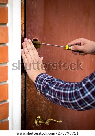 Closeup shot of carpenter fixing door lock with screwdriver - stock photo