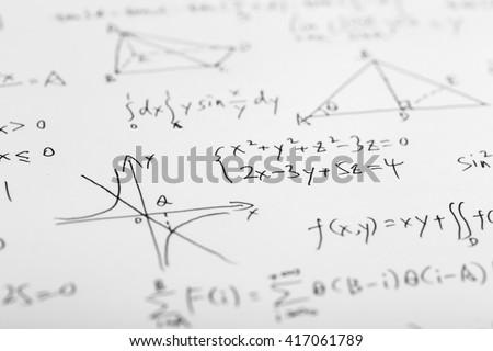 Closeup shot of complex math formulas on whiteboard. - stock photo