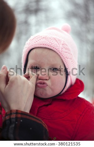 Closeup shot of crying baby girl, mother is wiping tears from her face. - stock photo