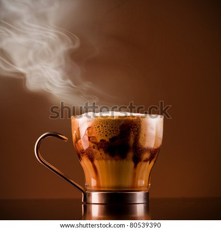 Closeup shot of Delicious smoking hot coffee drink macchiato, espresso with steamy milk and froth and added chocolate syrup for layered effect. Served on a bar in a glass cup. Textured background - stock photo