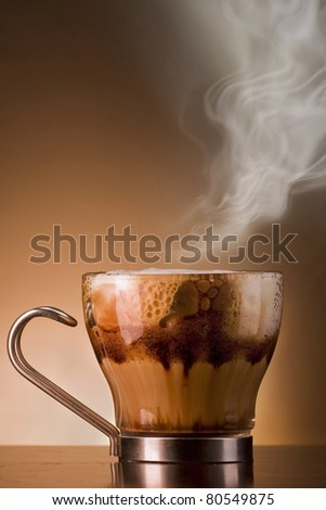 Closeup shot of Delicious smoking hot coffee drink macchiato, espresso with steamy milk and froth and added chocolate syrup for layered effect. Served on a bar in a glass cup. Lots of copyspace. - stock photo
