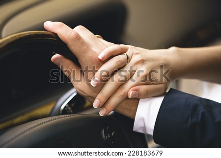 Closeup shot of elegant woman holding hand on men hand while he drives a car - stock photo