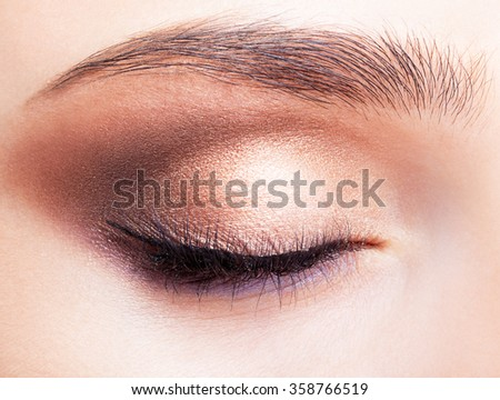 Closeup shot of female closed eye and brows with day makeup - stock photo