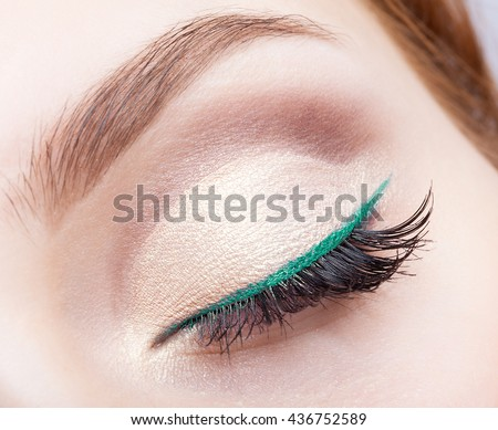 Closeup shot of female face makeup with closed eye and green eyeliner