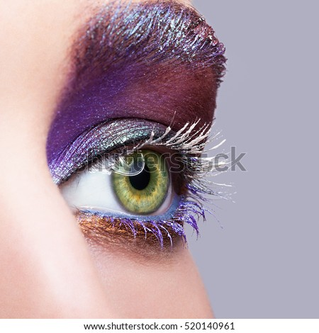 Closeup shot of female green pistachio colour eye  with evening violet purple  eyes shadows and white eyelashes makeup