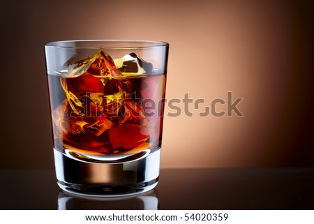 Closeup shot of glass filled with whiskey and ice, shot on rich background with space for copy