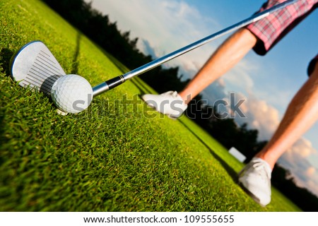 closeup shot of golf ball with golf club right before tee off, dynamically tilted picture - stock photo