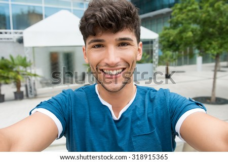 Closeup shot of handsome young man take a selfie in the city center. Guy is photographing self outdoor. Shallow depth of field with focus on smiling young man taking selfie.  - stock photo