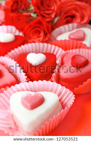Closeup shot of heart shaped sweets with the red roses in the background