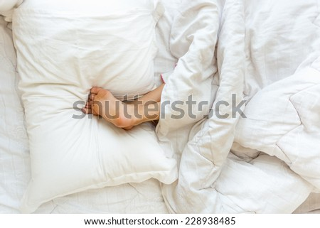 Closeup shot of little girl sleeping upside down and holding feet on pillow - stock photo