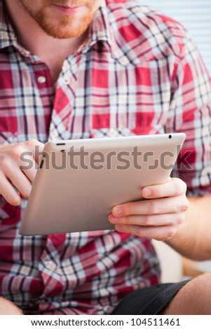 Closeup shot of male hands using a tablet - stock photo