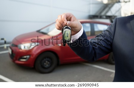 Closeup shot of man in suit showing car keys with alarm remote control - stock photo