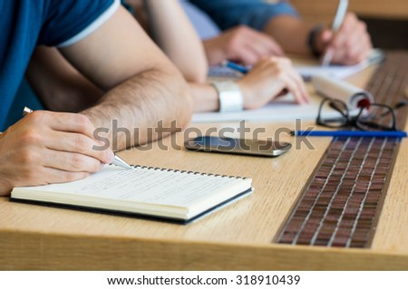 Closeup shot of man taking down note in diary. Close up of man's hand writing on notebook. Shallow depth of field with focus on man hand writing note in diary.  - stock photo