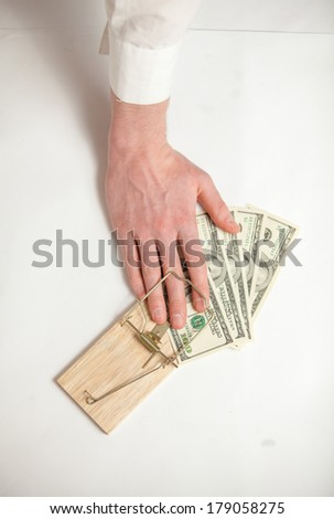 Closeup shot of men hand got caught in mouse trap while he was stealing money - stock photo