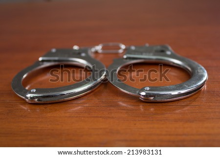Closeup shot of metallic handcuffs on wood background - stock photo