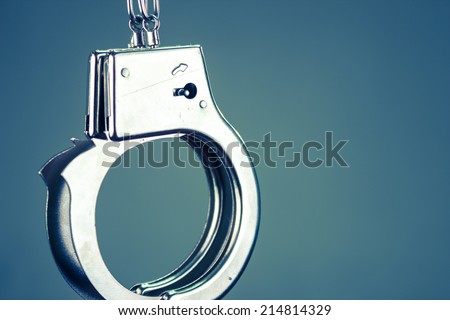 Closeup shot of metallic handcuffs over blue background color toned - stock photo
