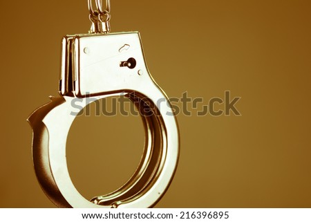 Closeup shot of metallic handcuffs over brown background color toned - stock photo