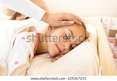 Closeup shot of mother holding hand on daughters head at bed