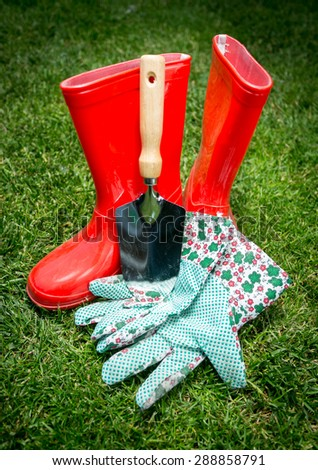 Closeup shot of small spade, gloves and red rubber boots lying on green grass - stock photo