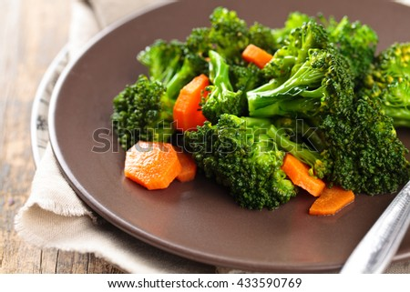 Closeup shot of steamed carrots and broccoli  on plate.  - stock photo
