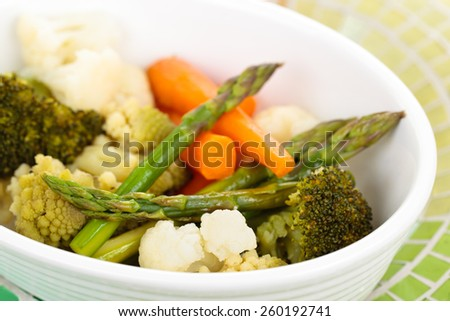 Closeup shot of steamed vegetables on white plate. Focus on asparagus tips on the left. - stock photo