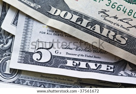 closeup shot of US currencies with focus on five dollar bill