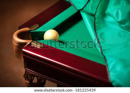 Closeup shot of white ball in billiard pocket on partly covered table with cloth - stock photo
