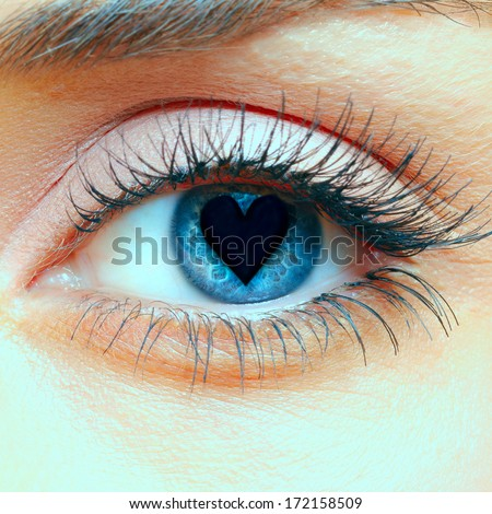 Closeup shot of woman eye with heart in the pupil - stock photo