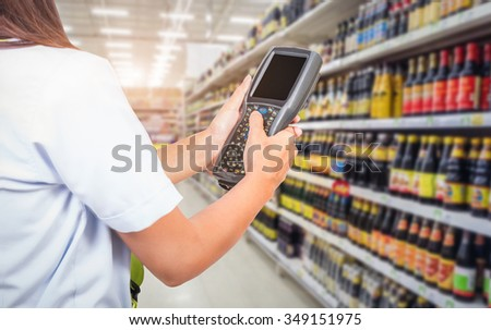 Closeup shot of worker scanning box with barcode reader. Reading and Scanning labels on the boxes with bluetooth barcode scanner in a warehouse. - stock photo