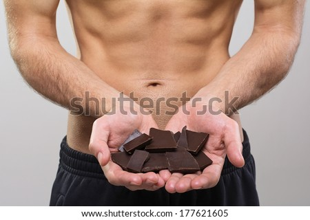 Closeup shot of young fit man's hands holding dark chocolate pieces. Fit abs in the background. Diet, nutrition, healthy food concept. - stock photo