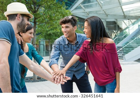 Closeup shot of young friends making huddle with their hand. Happy smiling friends. Happy young friends making huddle. Portrait of a group of people with their hands stacked in a city center. - stock photo