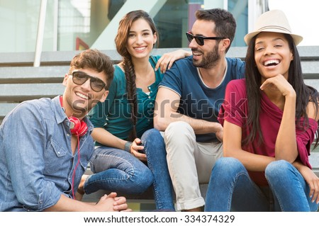 Closeup shot of young friends sitting on staircase having fun. Happy girls and guys smiling and looking at camera. Young men and young women stay together. - stock photo