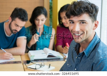 Closeup shot of young man looking at camera. Happy male student in casual smiling. Shallow depth of field with focus on handsome young man smiling with other student in background. - stock photo