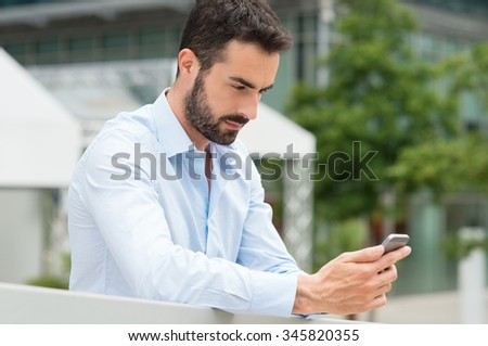 Closeup shot of young man messaging on smartphone. Happy smiling businessamn looking at smart phone leaning against a railing outdoor. Handsome young man using cellphone in a urban scene. - stock photo