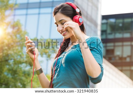 Closeup shot of young woman listening to music with mobile phone outdoor. Happy smiling girl listening to music with earphone. Portrait of carefree woman listening to music in a city center. - stock photo