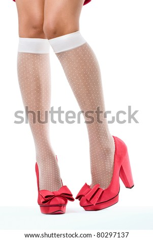 Closeup shot of young woman's legs in fashionable high heel red shoes and white stockings, on white - stock photo