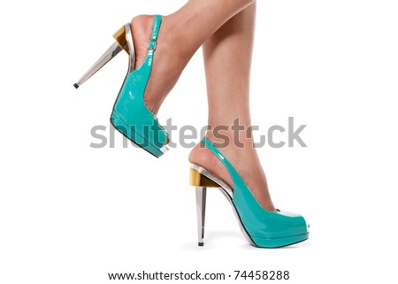 Closeup shot of young woman's legs in fashionable high heel turquoise shoes, on white - stock photo