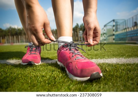 Closeup shot of young woman tying shoe laces before running - stock photo