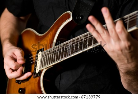 closeup shots of hands playing on a guitar